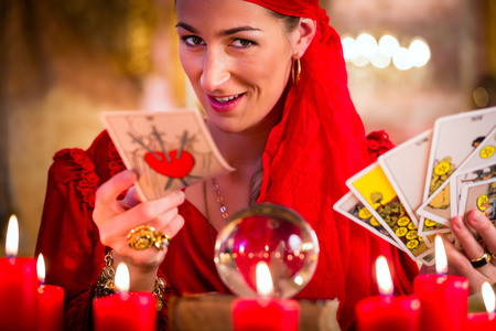 foresee: Fortuneteller with Tarot cards or esoteric Oracle, sees in the future Stock Photo