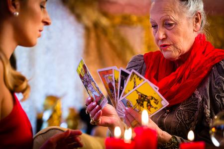 astrologie: Fortuneteller legen Tarot-Karten mit Client auf Pentagramm, werden Kerzen brennen Lizenzfreie Bilder