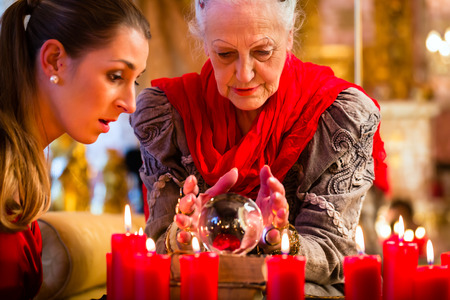Female Fortuneteller or esoteric Oracle, sees in the future by looking into their crystal ball answering questions from client photo