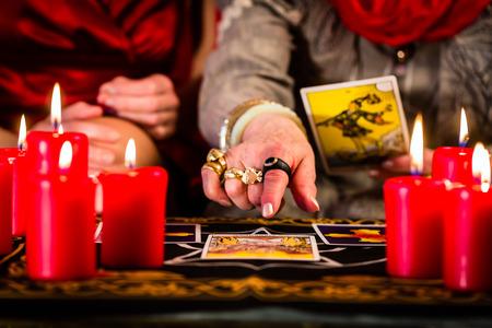 soothsayer: Adivino que pone las cartas del Tarot con el cliente en pentagrama, velas están quemando Foto de archivo