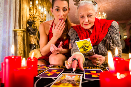 Fortuneteller laying Tarot cards with client on pentagram, candles are burning photo
