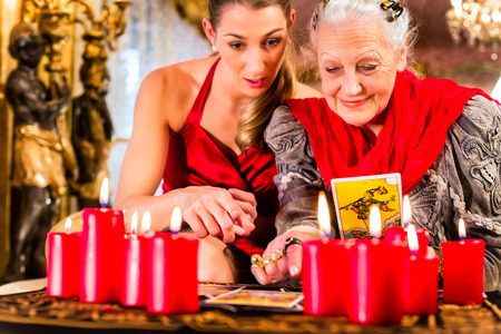 to foresee: Fortuneteller laying Tarot cards with client on pentagram, candles are burning