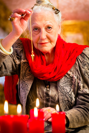 Fortuneteller dowsing with pendulum looking into the future photo