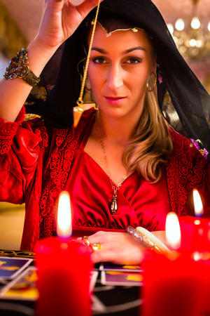 clairvoyance: Fortuneteller radiesthesist in Seance dowsing with pendulum telling the future Stock Photo