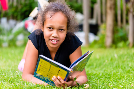 fille noire: Noir fille livre de lecture sur la prairie couch� dans l'herbe