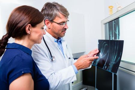 ortopedia: Doctor con el cuadro de la radiografía de la mano del paciente en su cirugía examinar la imagen