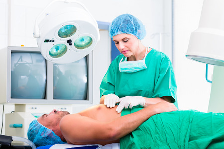 Orthopedic surgeon doctor operating patient in surgery or hospital Stock Photo