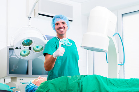 orthopedics: Doctor having successful operation in operating room giving thumbs up