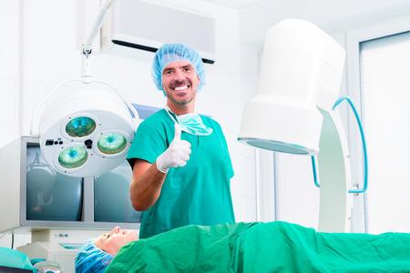 ortopedia: Doctor que tiene exitosa operación en quirófano dando pulgar hacia arriba Foto de archivo