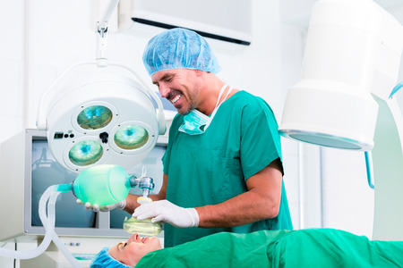 Doctor surgeon with patient in operating room applying anesthetic with mask