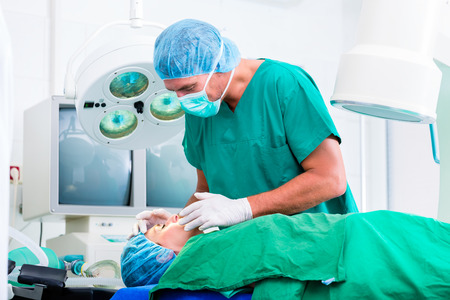 anesthesia: Doctor surgeon with patient in operating room applying anesthetic with mask