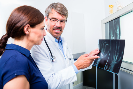 orthopedics: Doctor with x-ray picture of patient hand in his surgery examining the image Stock Photo