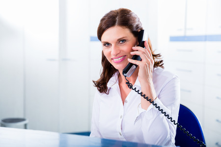front office: Doctors nurse with telephone in front desk making appointment with patient