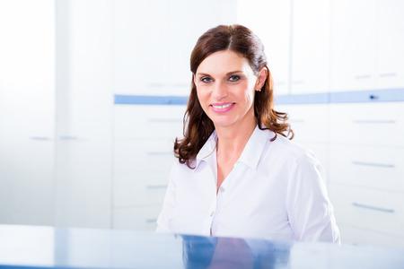 Artsen verpleegkundige met telefoon in de receptie maken van afspraak met de patiënt