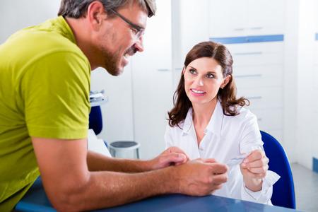 Médicos enfermeira com telefone em recepção fazendo entrevista com paciente Imagens