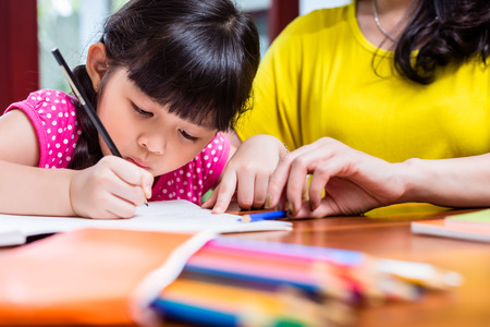 learning: Chinese mother homeschooling her child teaching her daughter to write