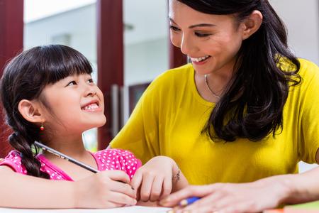 niños escribiendo: Madre china educación en el hogar a su hijo enseña a su hija a escribir Foto de archivo