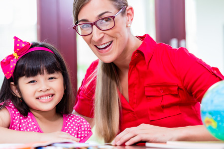 kids learning: Teacher giving language lessons and doing homework to Chinese child