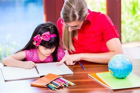 Učitel dává jazykové kurzy a dělat domácí úkoly na čínské dítě Reklamní fotografie