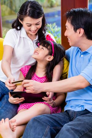 ni�os de compras: Familia de compras en l�nea de China con tablet PC y la tarjeta de cr�dito