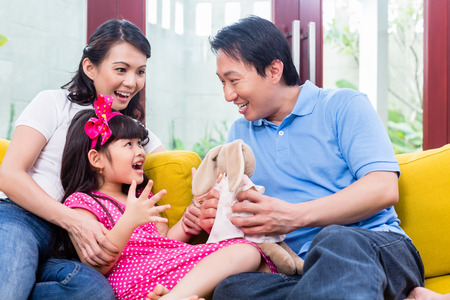 stuffed animal: Chinese Family playing with daughter on sofa holding stuffed animal