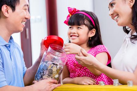einsparung: Chinesische Familie, Geld zu sparen für College Fund des Kindes, die Münzen im Glas