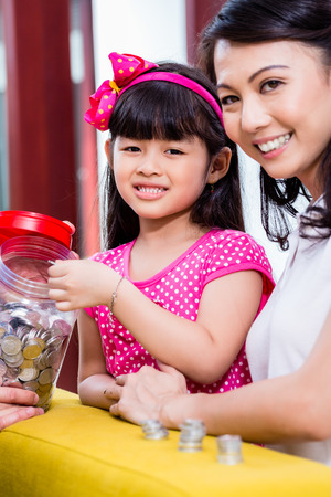 asian coins: Chinese family saving money for college fund of child, putting coins in jar