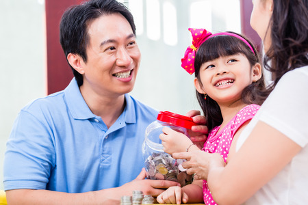 college fund savings: Chinese family saving money for college fund of child, putting coins in jar