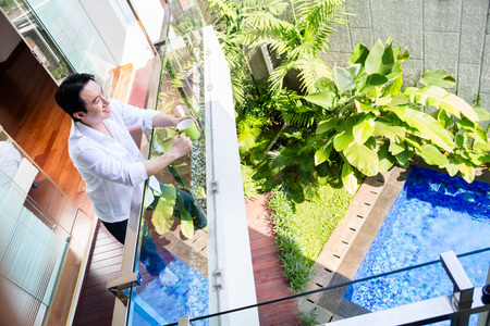 Chinese man on balcony of home with coffee looking at garden pool Reklamní fotografie