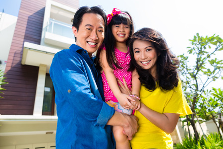 happy asian people: Asian Chinese family of parents and child standing proud in front of  modern home
