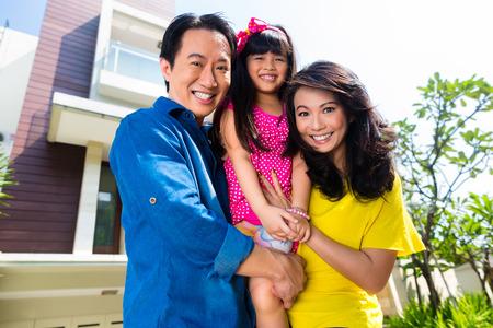 asia smile: Familia china asi�tica de los padres y el ni�o de pie, orgullosos frente a la casa moderna Foto de archivo