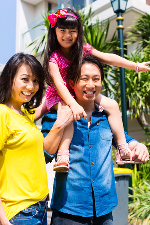 asian family home: Asian Chinese family of parents and child standing proud in front of  modern home