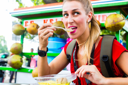 asia: European Woman eating at mobile kitchen stall on Jakarta travel exploring Indonesia street food Stock Photo