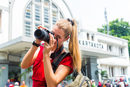 photographing: Woman photographing train station sightseeing with camera in Jakarta, Indonesia Stock Photo