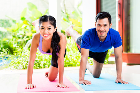 home trainer: Asian man and woman in fitness exercise at home Stock Photo