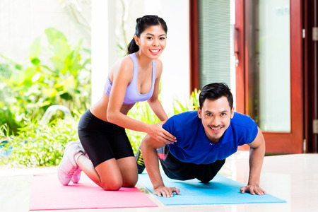 pushup: Asian woman helping man with push-up to gain better fitness Stock Photo