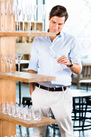 furniture store: Man in furniture store choosing glasses standing in wooden shelf