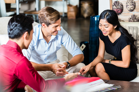 furniture store: Couple of Caucasian man and Asian woman and shop assistant in furniture store planning furnishing of home together