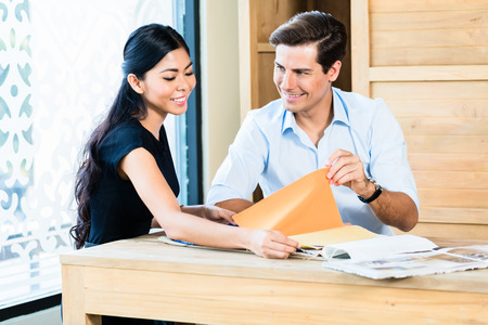 furniture store: Mixed Asian Caucasian couple in furniture store or showroom choosing color and material for furnishing