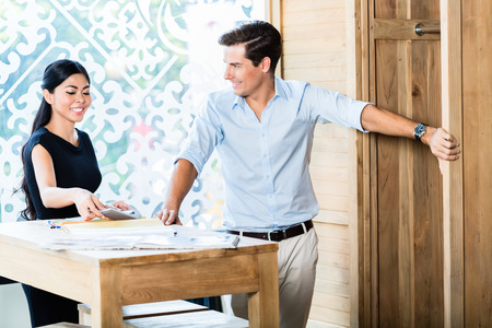 Mixed Asian Caucasian couple in furniture store or showroom calculating price, she is showing calculator to him Stock Photo