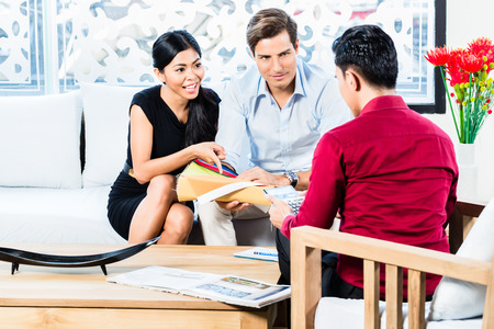 Mixed couple in furniture store with shop assistant discussing colors and material of items they are buying 스톡 콘텐츠