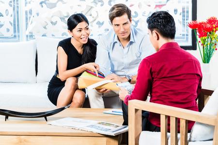 couple mixte: Couple mixte en magasin de meubles avec des couleurs vendeuse discuter et de mat�riel d'articles qu'ils ach�tent