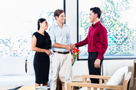 Mixed couple in furniture store with Asian shop assistant shaking hands sealing deal