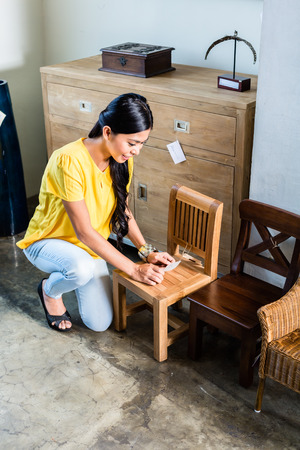 house shopping: Asian woman in furniture store buying chair