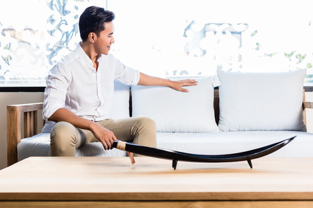 furniture: Asian Indonesian man sitting on sofa couch in furniture store showroom