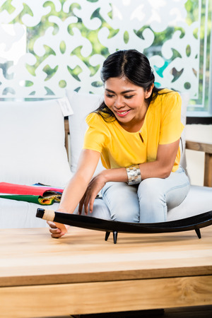 furniture store: Asian Indonesian woman sitting on sofa couch in furniture store showroom with color and material catalog Stock Photo