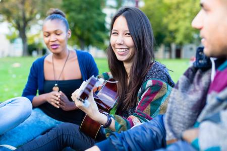 canto: Amigos que cantan canciones en el parque que se divierte junto con una ni�a de tocar la guitarra, el grupo de diversidad de �frica, Asia y las personas de raza blanca