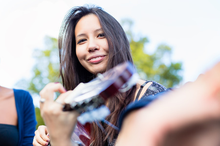 making music: Guitar player Asian girl making music with friends in park Stock Photo