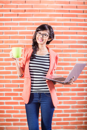 coder: Asian college student with Laptop and coffee standing in front of brick wall Stock Photo