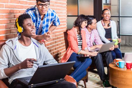 コーディングのスタートアップ企業でのコンピューター プログラマー、同僚は彼の肩越しに見ています。